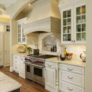 Exempel på ett mycket stort klassiskt kök, med en rustik diskho, luckor med profilerade fronter, vita skåp, granitbänkskiva, beige stänkskydd, stänkskydd i sten, rostfria vitvaror, mörkt trägolv, en köksö och brunt golv