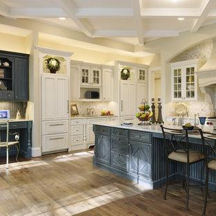 Idéer för mycket stora vintage l-kök, med en rustik diskho, luckor med profilerade fronter, vita skåp, granitbänkskiva, beige stänkskydd, stänkskydd i sten, rostfria vitvaror, mörkt trägolv, en köksö och brunt golv