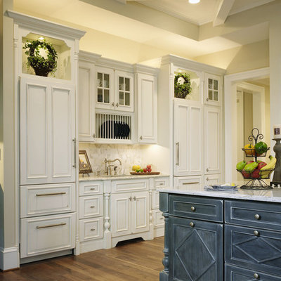 Eat-in kitchen - huge traditional l-shaped dark wood floor and brown floor eat-in kitchen idea in Baltimore with a farmhouse sink, beaded inset cabinets, white cabinets, granite countertops, beige backsplash, stone slab backsplash, stainless steel appliances and an island