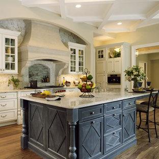 Geräumige Klassische Küche in L-Form mit Küchenrückwand in Beige, Rückwand aus Stein, Küchengeräten aus Edelstahl, Kücheninsel, Landhausspüle, Kassettenfronten, weißen Schränken, Granit-Arbeitsplatte, dunklem Holzboden und braunem Boden in Baltimore