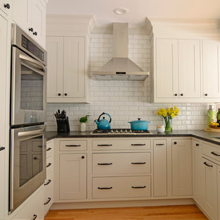 Small traditional u-shaped kitchen/diner in New York with a submerged sink, shaker cabinets, beige cabinets, granite worktops, white splashback, ceramic splashback, stainless steel appliances and a breakfast bar.
