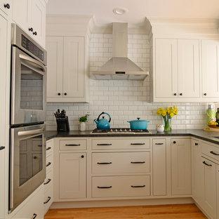 На фото: маленькая п-образная кухня в классическом стиле с обеденным столом, врезной раковиной, фасадами в стиле шейкер, бежевыми фасадами, гранитной столешницей, белым фартуком, фартуком из керамической плитки, техникой из нержавеющей стали и полуостровом с