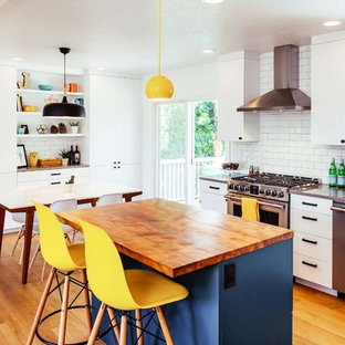 Mid-sized contemporary l-shaped eat-in kitchen in Portland with an undermount sink, flat-panel cabinets, white cabinets, quartz benchtops, white splashback, subway tile splashback, stainless steel appliances, vinyl floors, with island and brown floor.