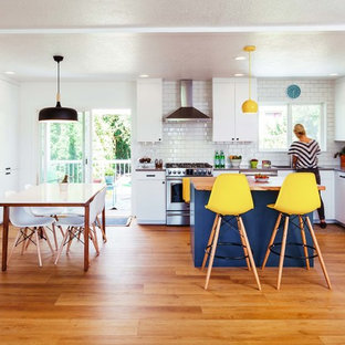 Photo of a medium sized contemporary l-shaped kitchen/diner in Portland with a submerged sink, flat-panel cabinets, white cabinets, engineered stone countertops, white splashback, metro tiled splashback, stainless steel appliances, vinyl flooring, an island and brown floors.