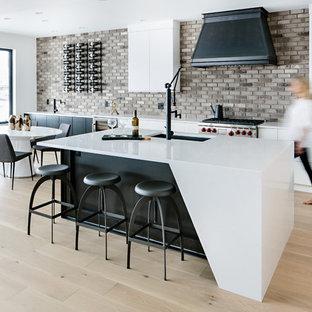 他の地域のコンテンポラリースタイルのおしゃれなキッチン (フラットパネル扉のキャビネット、白いキャビネット、茶色いキッチンパネル、レンガのキッチンパネル、シルバーの調理設備の、淡色無垢フローリング、アンダーカウンターシンク、ベージュの床、白いキッチンカウンター) の写真