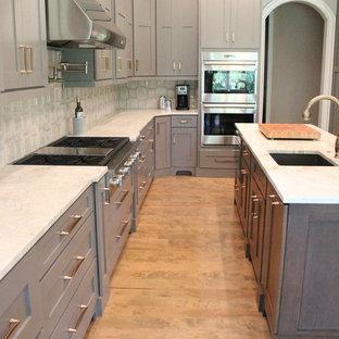 Inspiration för ett mycket stort funkis kök, med en rustik diskho, skåp i shakerstil, grå skåp, marmorbänkskiva, beige stänkskydd, stänkskydd i keramik, rostfria vitvaror, mellanmörkt trägolv, flera köksöar och brunt golv
