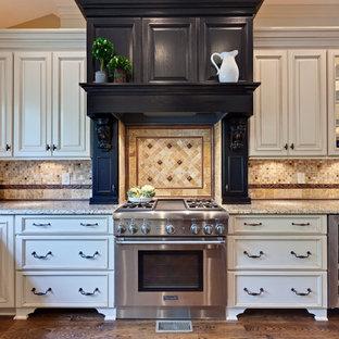 アトランタの広いトラディショナルスタイルのおしゃれなキッチン (レイズドパネル扉のキャビネット、白いキャビネット、トラバーチンのキッチンパネル、エプロンフロントシンク、御影石カウンター、マルチカラーのキッチンパネル、シルバーの調理設備、無垢フローリング、茶色い床、ベージュのキッチンカウンター) の写真