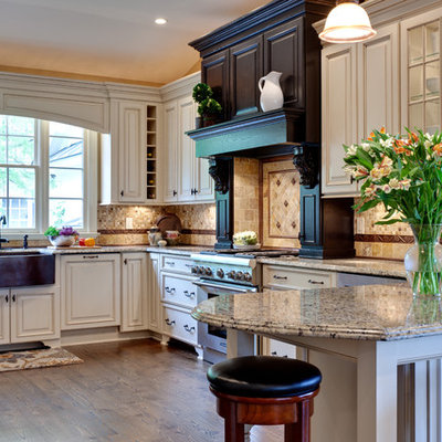 Example of a large classic u-shaped medium tone wood floor and brown floor eat-in kitchen design in Atlanta with raised-panel cabinets, stainless steel appliances, a farmhouse sink, white cabinets, granite countertops, multicolored backsplash, stone tile backsplash, a peninsula and beige countertops