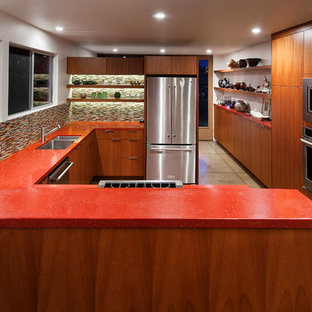 This is an example of a mid-sized midcentury u-shaped eat-in kitchen in Los Angeles with an undermount sink, flat-panel cabinets, medium wood cabinets, quartz benchtops, multi-coloured splashback, glass tile splashback, stainless steel appliances, a peninsula and red benchtop.