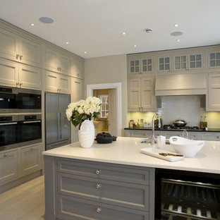 Transitional kitchen in London with an undermount sink, recessed-panel cabinets, grey cabinets, white splashback and stainless steel appliances.