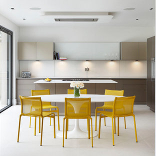 Medium sized contemporary galley kitchen/diner in London with flat-panel cabinets, brown cabinets, quartz worktops, integrated appliances, an island, grey floors and white splashback.