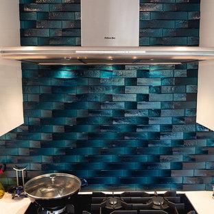 ロサンゼルスの広いモダンスタイルのおしゃれなキッチン (アンダーカウンターシンク、フラットパネル扉のキャビネット、中間色木目調キャビネット、クオーツストーンカウンター、青いキッチンパネル、ガラスタイルのキッチンパネル、シルバーの調理設備、磁器タイルの床、グレーの床、白いキッチンカウンター) の写真