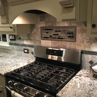 Mid-sized traditional enclosed kitchen designs - Example of a mid-sized classic l-shaped medium tone wood floor enclosed kitchen design in Atlanta with an undermount sink, beaded inset cabinets, white cabinets, granite countertops, beige backsplash, stone tile backsplash, black appliances and an island
