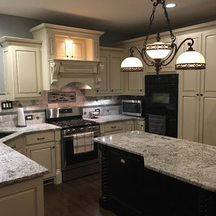 Mid-sized traditional enclosed kitchen appliance - Example of a mid-sized classic l-shaped medium tone wood floor and brown floor enclosed kitchen design in Atlanta with an undermount sink, beaded inset cabinets, white cabinets, granite countertops, beige backsplash, stone tile backsplash, black appliances and an island