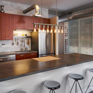 Immagine di una grande cucina industriale con lavello sottopiano, ante lisce, ante rosse, top in cemento, paraspruzzi grigio, paraspruzzi in marmo, elettrodomestici in acciaio inossidabile, parquet scuro, penisola e pavimento marrone