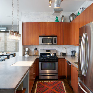 シカゴの大きいインダストリアルスタイルのおしゃれなキッチン (アンダーカウンターシンク、フラットパネル扉のキャビネット、赤いキャビネット、コンクリートカウンター、グレーのキッチンパネル、大理石の床、シルバーの調理設備の、濃色無垢フローリング、茶色い床) の写真