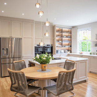 Inspiration for an expansive classic l-shaped kitchen/diner in Other with a submerged sink, shaker cabinets, grey cabinets, stainless steel appliances, medium hardwood flooring, an island, brown floors and white worktops.