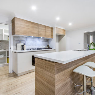 Design ideas for a contemporary galley kitchen in Canberra - Queanbeyan with a double-bowl sink, flat-panel cabinets, light wood cabinets, grey splashback, light hardwood floors, with island, beige floor and white benchtop.