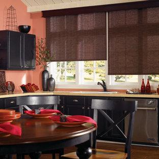 ニューオリンズの中サイズのコンテンポラリースタイルのおしゃれなキッチン (ドロップインシンク、レイズドパネル扉のキャビネット、黒いキャビネット、タイルカウンター、ピンクのキッチンパネル、木材のキッチンパネル、シルバーの調理設備の、無垢フローリング、アイランドなし) の写真