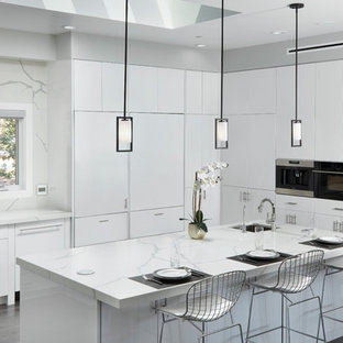 Large contemporary kitchen remodeling - Inspiration for a large contemporary u-shaped brown floor and dark wood floor kitchen remodel in Los Angeles with an undermount sink, flat-panel cabinets, white cabinets, quartz countertops, paneled appliances, an island and white backsplash