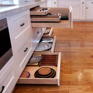 Mittelgroße Urige Küche in L-Form mit Unterbauwaschbecken, Schrankfronten im Shaker-Stil, weißen Schränken, Küchengeräten aus Edelstahl, hellem Holzboden, Quarzit-Arbeitsplatte, Küchenrückwand in Weiß, Rückwand aus Stein, Kücheninsel und beigem Boden in Los Angeles