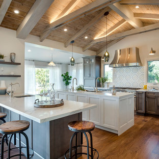 This is an example of a large country galley open plan kitchen in Los Angeles with quartz benchtops, multi-coloured splashback, stainless steel appliances, multiple islands, medium hardwood floors, raised-panel cabinets, dark wood cabinets, cement tile splashback, brown floor, an undermount sink and white benchtop.