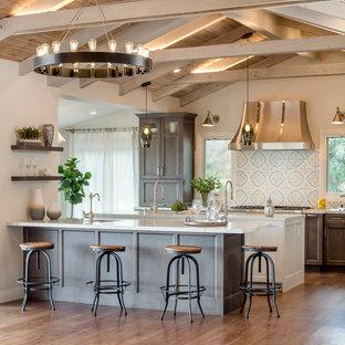 Große, Offene, Zweizeilige Landhausstil Küche mit Quarzwerkstein-Arbeitsplatte, bunter Rückwand, Küchengeräten aus Edelstahl, braunem Holzboden, zwei Kücheninseln, Unterbauwaschbecken, profilierten Schrankfronten, dunklen Holzschränken, Rückwand aus Zementfliesen, braunem Boden und weißer Arbeitsplatte in Los Angeles