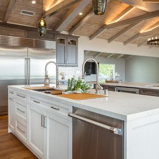 Lantlig inredning av ett stort vit vitt kök, med bänkskiva i kvarts, flerfärgad stänkskydd, rostfria vitvaror, mellanmörkt trägolv, flera köksöar, en undermonterad diskho, luckor med upphöjd panel, skåp i mörkt trä, stänkskydd i cementkakel och brunt golv