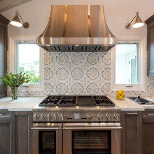 Inredning av ett lantligt stort vit vitt kök, med bänkskiva i kvarts, flerfärgad stänkskydd, rostfria vitvaror, mellanmörkt trägolv, flera köksöar, en undermonterad diskho, luckor med upphöjd panel, skåp i mörkt trä, stänkskydd i cementkakel och brunt golv