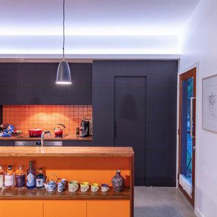 Свежая идея для дизайна: маленькая параллельная кухня-гостиная в современном стиле с накладной раковиной, плоскими фасадами, черными фасадами, деревянной столешницей, оранжевым фартуком, фартуком из керамогранитной плитки, техникой из нержавеющей стали, бетонным полом, островом и серым полом - отличное фото интерьера