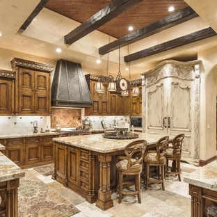 Inspiration for a large mediterranean u-shaped eat-in kitchen in Phoenix with a double-bowl sink, recessed-panel cabinets, dark wood cabinets, recycled glass benchtops, white splashback, porcelain splashback, stainless steel appliances, travertine floors and with island.