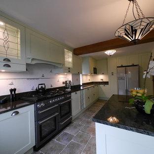 ロンドンの大きいカントリー風おしゃれなキッチン (アンダーカウンターシンク、シェーカースタイル扉のキャビネット、緑のキャビネット、御影石カウンター、白いキッチンパネル、セラミックタイルのキッチンパネル、黒い調理設備、ライムストーンの床、茶色い床、緑のキッチンカウンター) の写真