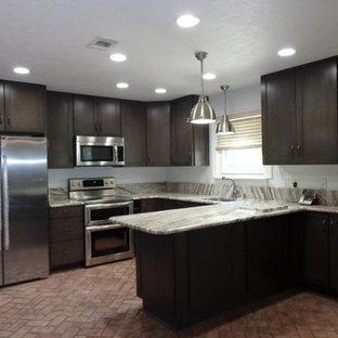 Inredning av ett klassiskt litet kök, med en undermonterad diskho, skåp i shakerstil, granitbänkskiva, brunt stänkskydd, stänkskydd i stenkakel, rostfria vitvaror, tegelgolv, en halv köksö, rött golv och bruna skåp