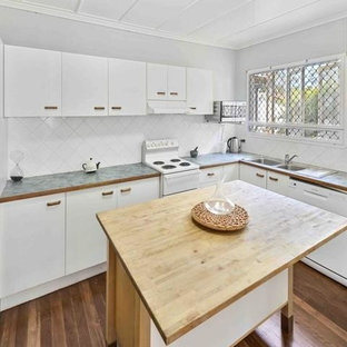 Design ideas for a mid-sized modern l-shaped separate kitchen in Brisbane with flat-panel cabinets, white cabinets, porcelain splashback, white appliances, medium hardwood floors, with island, a double-bowl sink, wood benchtops, white splashback and green benchtop.
