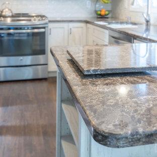 Foto på ett mellanstort kök, med en undermonterad diskho, luckor med infälld panel, vita skåp, bänkskiva i kvarts, vitt stänkskydd, rostfria vitvaror, plywoodgolv och en halv köksö