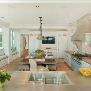 This is an example of a transitional l-shaped eat-in kitchen in Omaha with coloured appliances, an integrated sink, shaker cabinets and white cabinets.