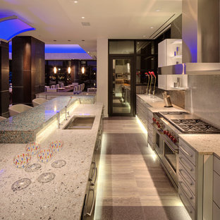 Inspiration for a contemporary galley eat-in kitchen in Milwaukee with an undermount sink, white cabinets, recycled glass benchtops, black splashback, metal splashback and stainless steel appliances.