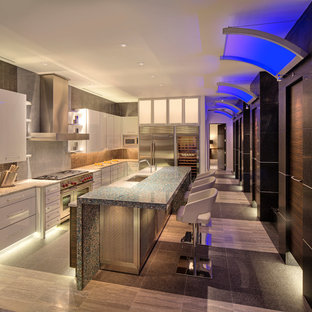 This is an example of a contemporary galley eat-in kitchen in Milwaukee with an undermount sink, white cabinets, recycled glass benchtops, black splashback, metal splashback and stainless steel appliances.