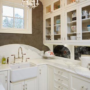 Inspiration for a small traditional u-shaped kitchen pantry in Grand Rapids with a farmhouse sink, glass-front cabinets, white cabinets, marble benchtops, white splashback, porcelain splashback, panelled appliances, multi-coloured benchtop, ceramic floors, no island and multi-coloured floor.