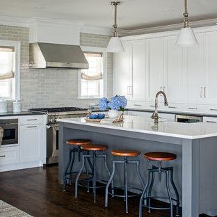 Diseño de cocina comedor marinera con armarios estilo shaker, puertas de armario blancas, salpicadero verde, electrodomésticos de acero inoxidable, suelo de madera oscura, una isla y suelo marrón