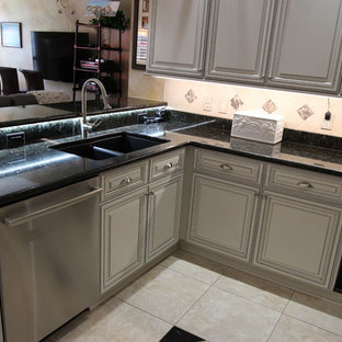 Design ideas for a mid-sized traditional u-shaped eat-in kitchen in Jacksonville with a double-bowl sink, raised-panel cabinets, white cabinets, granite benchtops, beige splashback, travertine splashback, stainless steel appliances, travertine floors, a peninsula, beige floor and black benchtop.