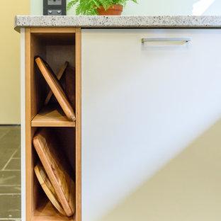 Свежая идея для дизайна: п-образная кухня-гостиная среднего размера в стиле модернизм с накладной раковиной, плоскими фасадами, светлыми деревянными фасадами, столешницей из ламината, синим фартуком, фартуком из стеклянной плитки, черной техникой, полом из сланца и полуостровом - отличное фото интерьера