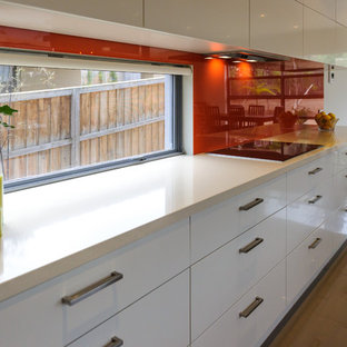 Large contemporary open concept kitchen remodeling - Example of a large trendy porcelain floor open concept kitchen design in Melbourne with an undermount sink, flat-panel cabinets, white cabinets, glass countertops, red backsplash, glass sheet backsplash and an island