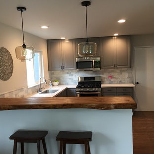 Design ideas for a mid-sized midcentury u-shaped eat-in kitchen in Santa Barbara with a single-bowl sink, raised-panel cabinets, grey cabinets, wood benchtops, grey splashback, stone tile splashback, stainless steel appliances, dark hardwood floors and a peninsula.