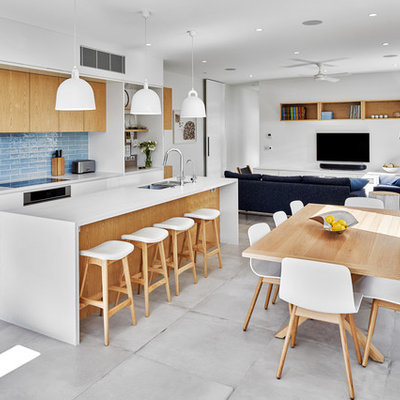 Trendy galley gray floor open concept kitchen photo in Sydney with an undermount sink, flat-panel cabinets, white cabinets, blue backsplash, stainless steel appliances, an island and white countertops