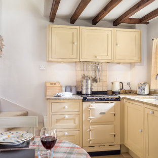 Inspiration for a country l-shaped kitchen/diner in Gloucestershire with a submerged sink, yellow cabinets, granite worktops, beige splashback, porcelain splashback, coloured appliances, no island and beaded cabinets.