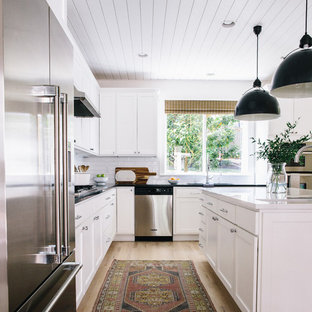 Inspiration for a mid-sized cottage l-shaped light wood floor and beige floor kitchen remodel in Seattle with an undermount sink, shaker cabinets, white cabinets, quartz countertops, white backsplash, ceramic backsplash, stainless steel appliances, an island and white countertops
