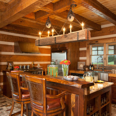 Open concept kitchen - large rustic l-shaped brick floor open concept kitchen idea in Other with a farmhouse sink, medium tone wood cabinets, glass countertops, brown backsplash, stainless steel appliances and an island
