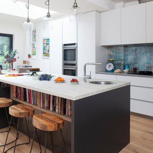Medium sized contemporary kitchen/diner in London with a submerged sink, flat-panel cabinets, white cabinets, blue splashback, medium hardwood flooring, an island, brown floors, grey worktops, marble worktops, metal splashback and stainless steel appliances.