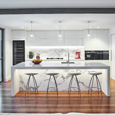 Trendy l-shaped medium tone wood floor open concept kitchen photo in Sydney with an undermount sink, flat-panel cabinets, white cabinets, stainless steel appliances, an island and marble backsplash